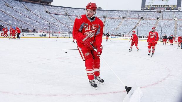 Justin Abdelkader of the Detroit Red Wings shovels snow during practice at Michigan Stadium.