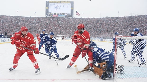 Pavel Datsyuk of the Detroit Red Wings, left, puts a shot on goaltender Jonathan Bernier of the Toronto Maple Leafs on January 1, 2014 at Michigan Stadium.