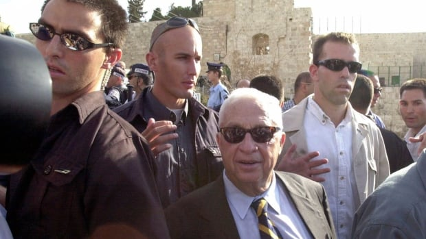 Israeli security officials guard then-opposition leader Ariel Sharon, centre, as he leaves the Temple Mount compound in East Jerusalem's Old City, in September 2000.  Sharon's career in Israeli politics has seen many successes, controversies and spectacular falls from power.