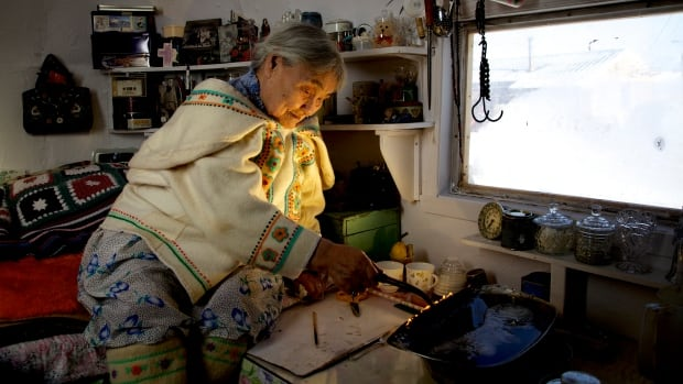 Qapik Attagutsiak of Arctic Bay, Nunavut, lights a qulliq — a traditional oil lamp — in her home.