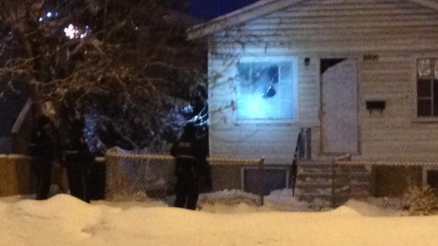 Saskatoon Police shine a light through the front window of a home on the 1400 block of 22nd Street West.