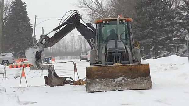 Crews dig up part of Laxdal Road on Friday, where a series of waterline breaks have left residents without water seven times in the past week.