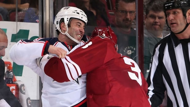 The Blue Jackets' Derek MacKenzie, left, fights with the Coyotes' Keith Yandle after knocking Phoenix defenceman Oliver Ekman-Larsson out of Thursday's game in the first period with a hit from behind. MacKenzie was suspended three games on Friday.