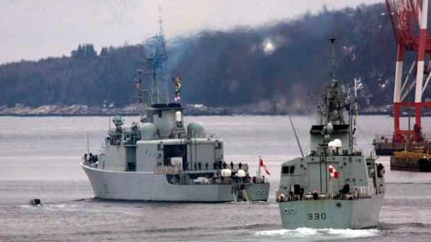 HMCS Halifax, right, and HMCS Athabaskan are pictured in this file photo out of the harbour in Halifax. They won't be moving on Friday. Most of the crews are off of the seven frigates and destroyers based in Halifax as a storm hits Halifax.