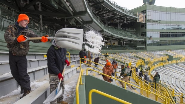 Workers clear ice and snow from the seats at Lambeau Field in preparation for Sunday's NFL football wild-card playoff game between the Green Bay Packers and San Francisco 49ers.