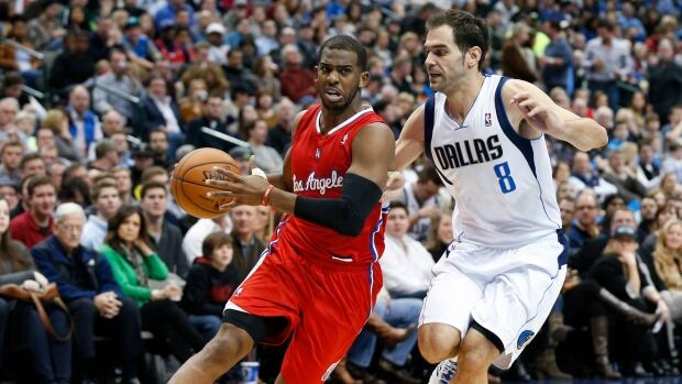 Los Angeles Clippers guard Chris Paul, left, controls the ball as Dallas Mavericks guard Jose Calderon, right, defends during the first half on Jan. 3, 2014.