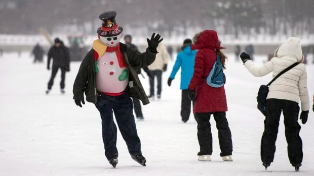 Luc Guertin, dressed in a snowman costume nicknamed Waldo Jr., waves to fellow skaters as he makes his way along the Rideau Canal on its opening day in Ottawa on Tuesday, Dec. 31, 2013.