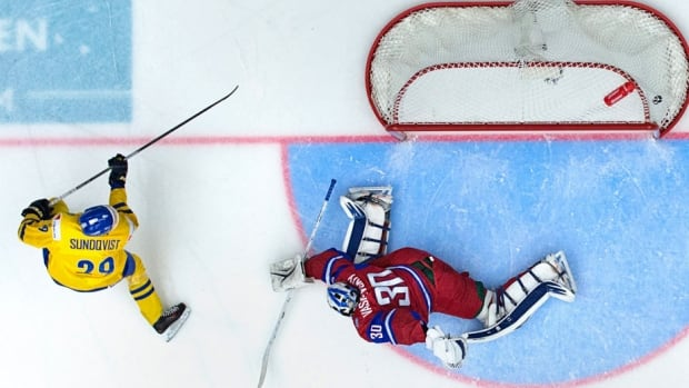 Sweden's Oskar Sundqvist scores on Russian goaltender Andrei Vasilevski during the world juniors semifinal at Malmo Arena in Malmo, Sweden on Saturday.