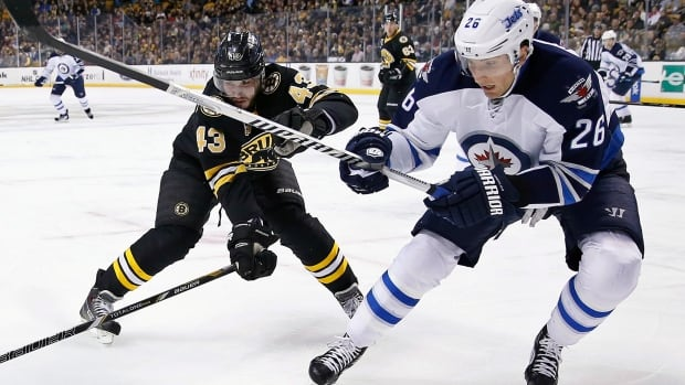Boston Bruins' Matt Bartkowski and Winnipeg Jets' Blake Wheeler battle for the puck in their only other match-up this year, on Jan. 4, 2014.