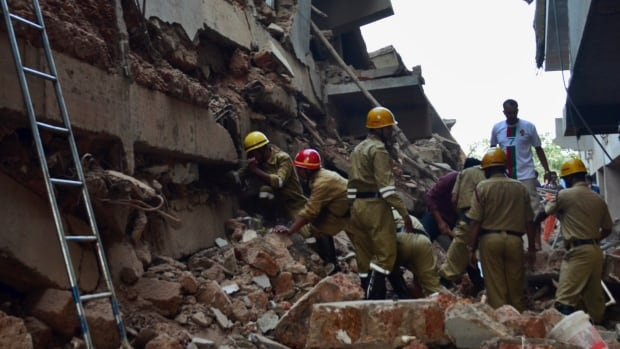 Rescue workers stand amid the debris of a building that collapsed in Canacona, a city about 70 kilometres from the state capital of Panaji, India. At least 14 workers were killed and dozens are feared to be trapped under the debris.
