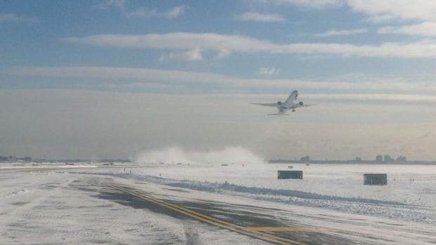 A plane from Toronto landed safely at John F. Kennedy International Airport on Sunday before sliding into snow as it turned onto a taxiway.