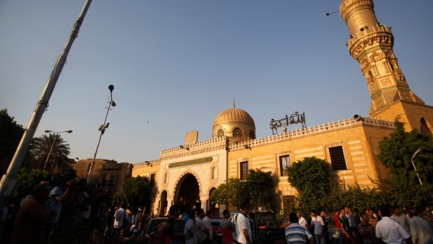 Egyptians stand outside El Sayeda Nafisa Mosque in Cairo. Sixty-one Canadian Shia Muslim pilgrims were detained by Egyptian authorities while en route to unspecified religious sites within the country.