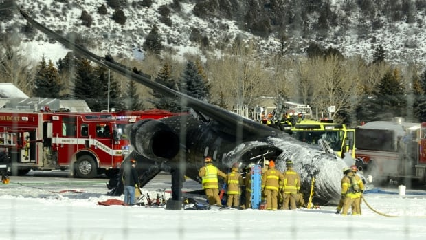 Emergency crews work near a passenger plane that crashed Sunday afternoon at the Aspen/Pitkin County Airport in Colorado.