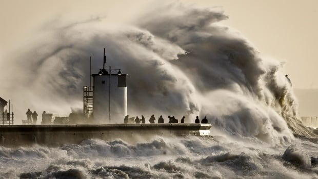 People watch and photograph enormous waves as they break, on Porthcawl harbour, South Wales in January, as storms and floods battered the country.The latest UN climate report says impacts of climate change, such as droughts and flooding 'might already be considered dangerous.'