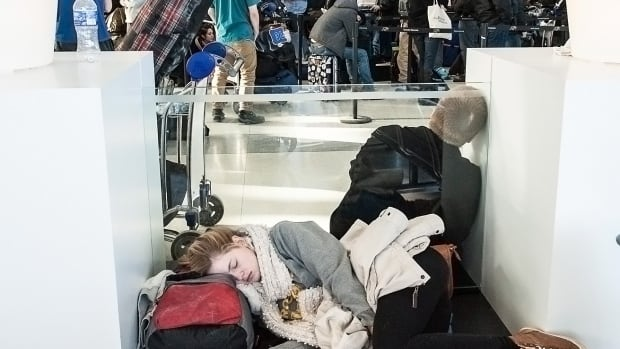 Exhausted passengers catch some sleep at Pearson airport in Toronto after extreme cold weather caused flight cancellations and long delays on Jan. 7.