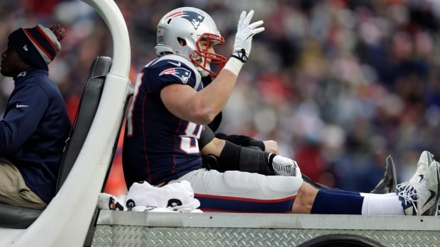 New England Patriots tight end Rob Gronkowski waves as he leaves the field in a cart after being injured a game against the Cleveland Browns on Dec. 8, 2013. Gronkowski will have surgery to repair his torn ACL and MCL on Thursday.