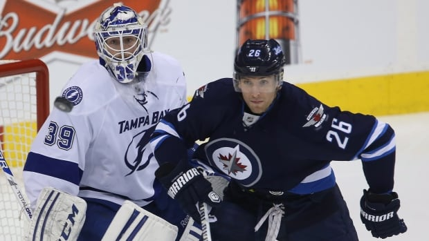 Tampa Bay Lightning goalie Anders Lindback and the Winnipeg Jets' Blake Wheeler watch a flying puck during the first period Tuesday at the MTS Centre.