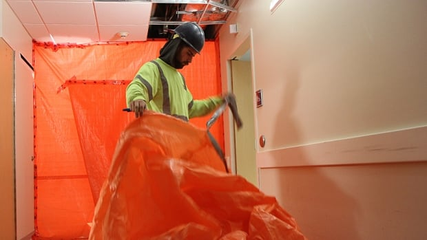 A construction worker cleans up flood damage at St. Joe's hospital in the diagnostic imaging unit on Thursday. The Hamilton hospital has been forced to cancel all surgeries at its Charlton Street building after a major Wednesday flood.