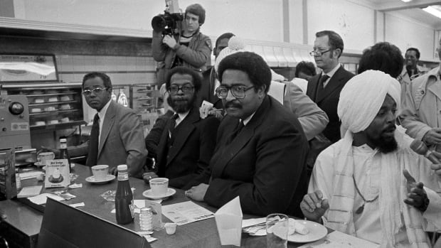 In a  Feb. 1, 1980, file photo, former North Carolina A&T students, left to right, Joseph McNeill, David Richmond, Franklin McCain and Jibreel Khazan, sit at the F.W. Woolworth lunch counter in Greensboro, N.C., as they celebrate the 20th anniversary of their historic sit-in. The four were not served in 1960 but their action launched  the sit-in movement in more than nine states.