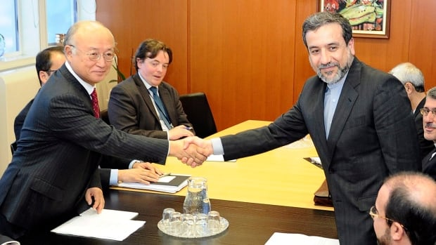 Iran's Deputy Foreign Minister Abbas Araghchi, right, shakes hands with Director General of the International Atomic Energy Agency Yukiya Amano at a meeting in Vienna, Austria, in October 2013. The nuclear deal struck by world powers and the Iranian government in November will be implemented on Jan. 20, the Iranian Foreign Ministry and the European Union said.