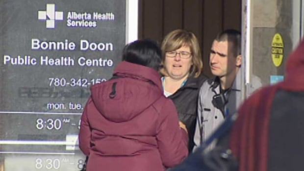 A woman talks to staff at the Bonnie Doon Health Clinic in Edmonton on Friday.