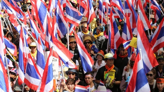 In this Nov. 7, 2013 photo, anti-government protesters wave Thai national flags and march on a street during a rally in Bangkok, Thailand. Anti-government protesters are planning to shut down Thailand's capital on Monday, Jan. 13, 2014 by blocking traffic at key intersections.