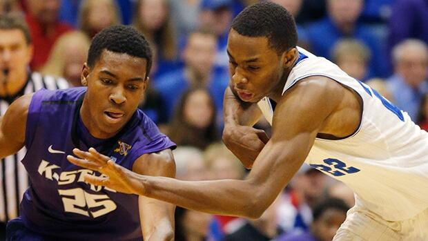 Kansas guard Andrew Wiggins, right, gets to the ball ahead of Kansas State's Wesley Iwundu during the first half in Lawrence, Kan., Saturday, Jan. 11, 2014.