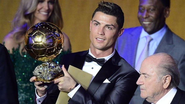 Real Madrid's Portuguese forward Cristiano Ronaldo poses with the 2013 FIFA Ballon d'Or award for player of the year next to FIFA president Sepp Blatter, bottom right, and France Football president Francois Moriniere, top right,  in Zurich, Switzerland on Monday.
