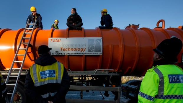 Police prepare to remove a protester from the top of a vehicle waiting to enter an exploratory drill site for the controversial gas extraction process known as fracking in Manchester, England, on Monday.