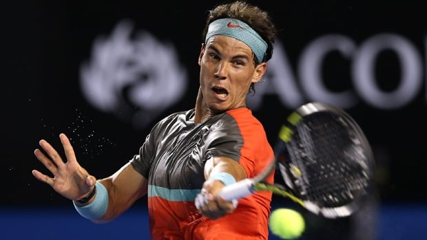 Top-ranked Rafael Nadal rips a forehand in Tuesday's triumph over Bernard Tomic, who retired after losing the opening set, 6-4.