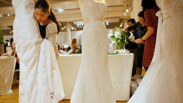 A wedding dress vendor prepares dresses for a wedding show in New York.