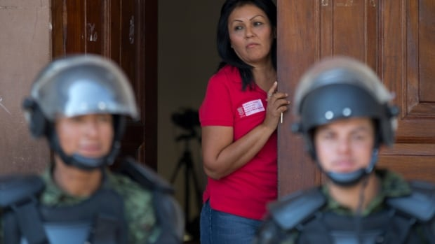 A cordon of soldiers guard City Hall in Apatzingan, Mexico, on Tuesday as Mexican soldiers and federal police kept a tense standoff with vigilantes after a new government campaign to stop violence in the western Michoacan state turned deadly.