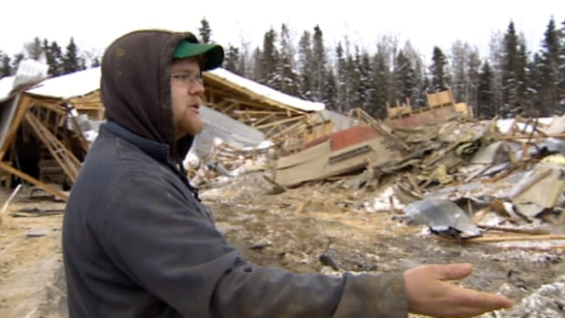 Dairy farmer Devon Semmelink shows the barn that collapsed under the weight of heavy snow last month.