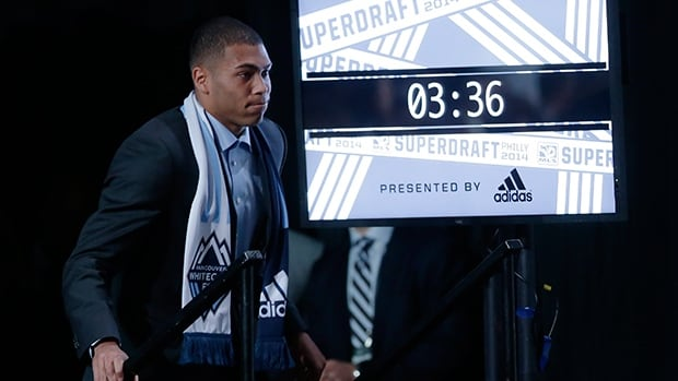 Christian Dean walks to the stage after being selected by Vancouver Whitecaps FC during the 2014 MLS SuperDraft, Thursday, Jan. 16, 2014, in Philadelphia.