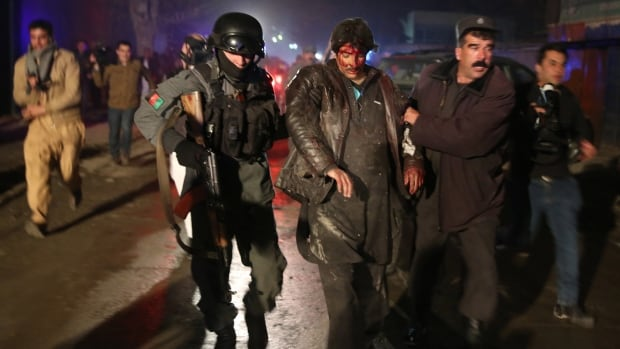 Afghan police forces assist an injured man at the site of a suicide attack in Kabul on Friday. The Taliban have claimed responsibility.