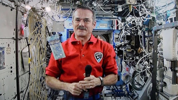 Astronaut Chris Hadfield poses for a photo with a new polymer $5 bank note on the International Space Station on April 30, 2013. The retired astronaut has been announced as a new CBC correspondent.