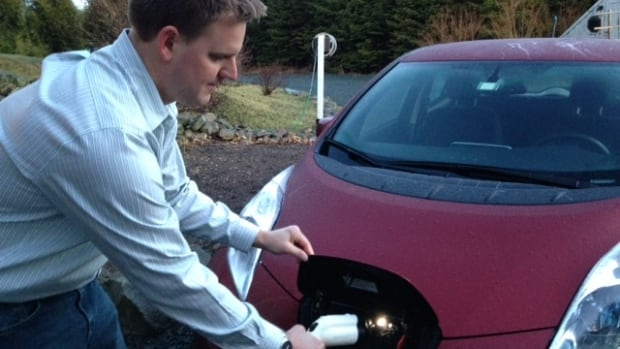 Lukas Swan plugs in his electric car to charge the battery.