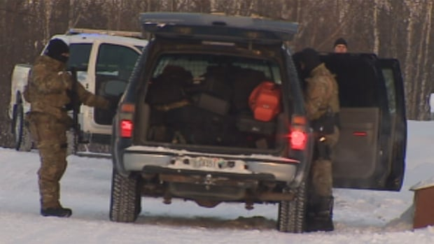 RCMP officers prepare to leave the scene of a standoff in Behchoko, N.W.T., Friday.