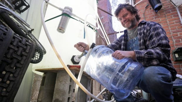 Jonathan Steele, owner of Bluegrass Kitchen, fills a jug with cleaning water in the back of his restaurant in Charleston, W.Va., on Jan. 14., after a chemical spill tainted the community's water supply. Freedom Industries, the company blamed for the spill, has filed for bankruptcy.
