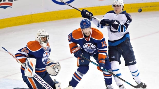 Winnipeg Jets' Mark Scheifele (55) and Edmonton Oilers' Nick Schultz (15) look for the rebound as goalie Ilya Bryzgalov (80) makes the save during third period NHL hockey action in Edmonton, Alta., on Monday December 23, 2013. THE CANADIAN PRESS/Jason Franson