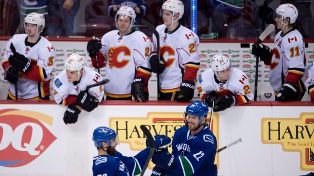 Members of the Calgary Flames look on as Vancouver Canucks left wing Chris Higgins (20) celebrates his game-winning shootout goal with teammate Daniel Sedin against the Calgary Flames on Jan. 18.