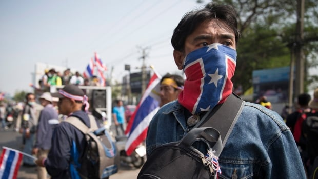 An anti-government protester takes part in a march in Bangkok on Sunday. Two explosions shook a demonstration site in the Thai capital, wounding at least 28 people.