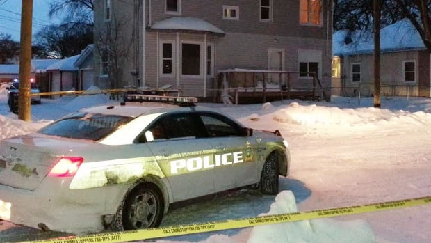Police investigate at a rooming house where a man's dead body was found on Sunday.
