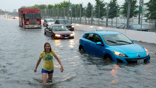 A woman wades through flood water on Lakeshore West during a storm in Toronto last July.  The unexpected flooding cost almost $1 billion in damages.
