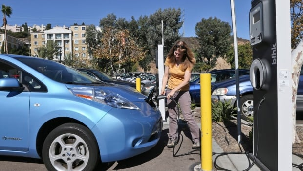 Angie Vorhies plugs in the charging cord to her Nissan Leaf electric vehicle  at a mall in November 2013 in San Diego.