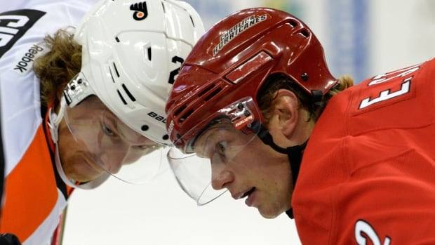 Fans in Philadelphia will have to wait a little longer to see the Flyers' Claude Giroux, left, battle the Hurricanes' Eric Staal, right, after a snowstorm forced the postponement of Tuesday's NHL matchup.