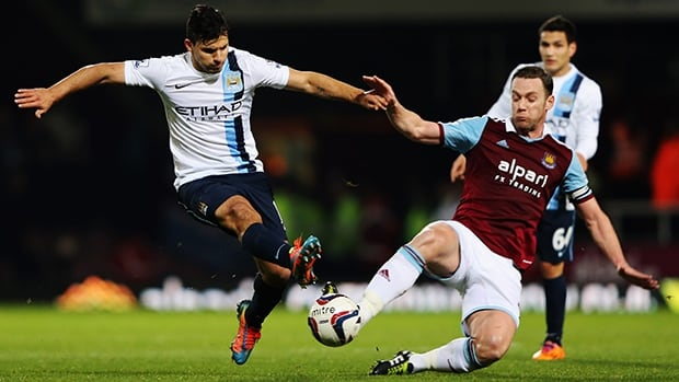 Sergio Aguero of Manchester City is tackled by Kevin Nolan of West Ham United on January 21, 2014 in London, England.