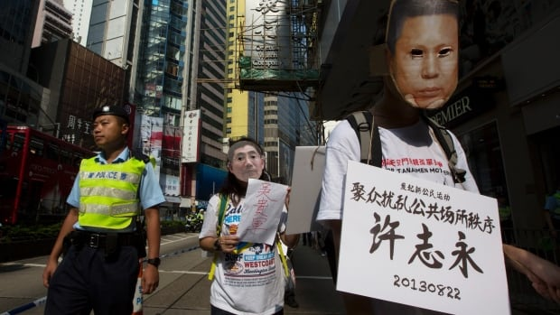 A pro-democracy protester marches in October 2013 wearing a mask depicting Chinese political prisoner Xu Zhiyong and carrying a placard that lists Xu's chargers. 'Xu Zhiyong - Disrupting Public Order,' reads the sign. Xu will be tried in a Beijing court Wednesday.