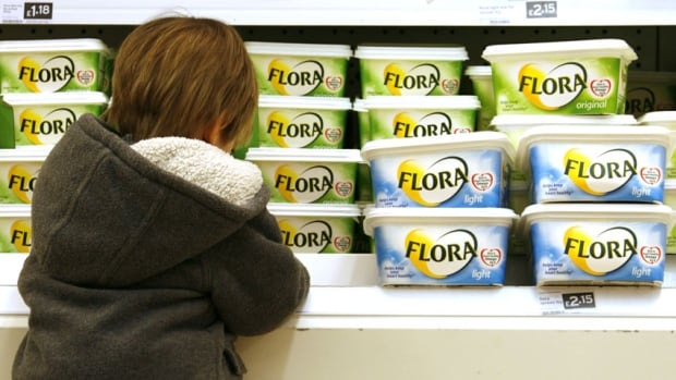 A child checks out the margarine section at a Sainsbury's supermarket in London, England. Flora is a brand owned by Unilever, which has decided to begin adding butter to one of its margarine products sold in Europe.
