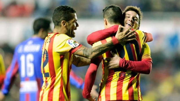 Barcelona forward Cristian Tello, second right, celebrates his third goal with Lionel Messi, right, and goalkeeper Victor Valdes during the Copa del Rey quarter-final first-leg match at the Ciutat de Valencia stadium in Valencia on Wednesday.